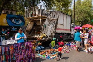 A garbage truck surrounded by street vendors